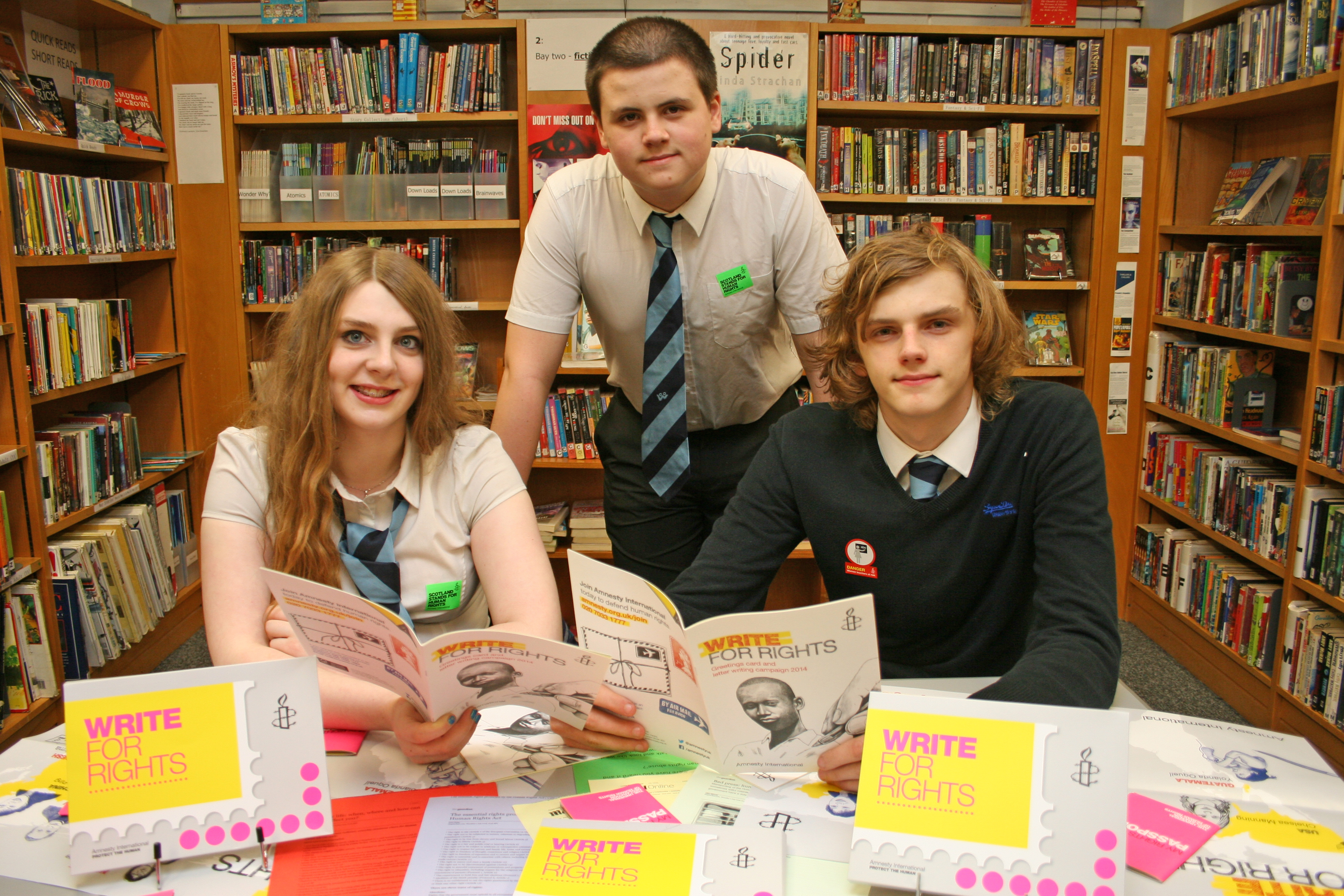 Students in school library with Amnesty Write for Rights literature